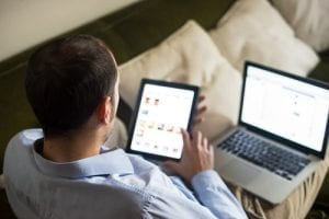 Man using an ipad and laptop to look at a responsive mobile friendly website