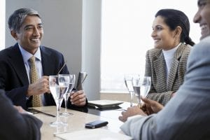 businessmen and women talking around a table